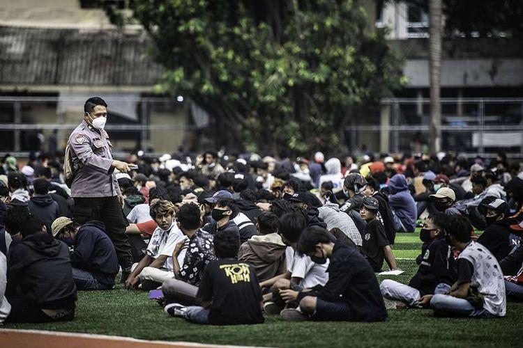 Petugas kepolisian mendata peserta aksi sebelum dipulangkan di Polda Metro Jaya, Jakarta, Rabu (14/10/2020). Polda Metro Jaya memulangkan ratusan peserta aksi yang diamankan dalam aksi unjuk rasa menolak UU Cipta Kerja.