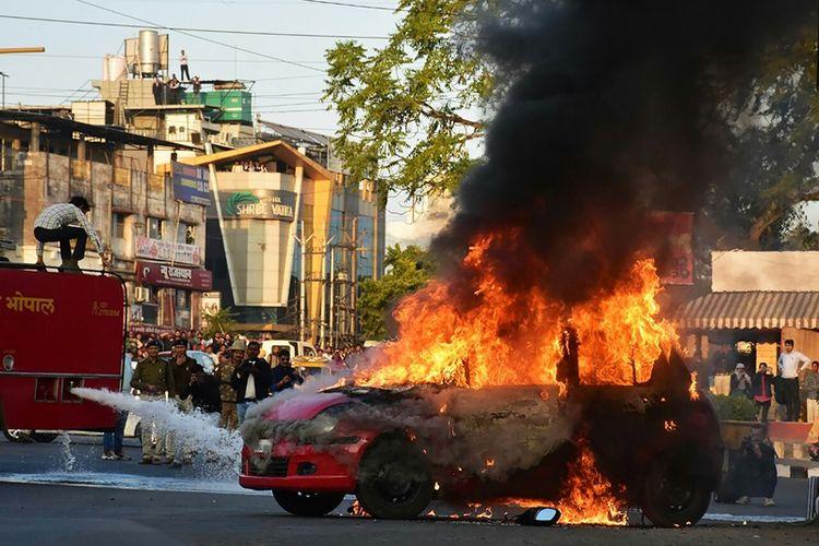 Sebuah mobil dibakar massa yang memprotes pemutaran film Padmavaat di kota Bhopal, India.