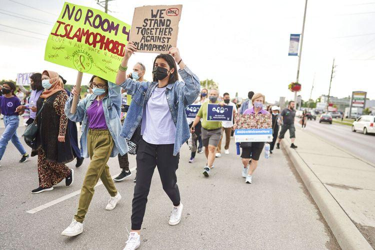 Dua wanita muda berjalan dengan membawa tanda-tanda ketika ribuan orang berbaris melalui jalan-jalan di London Ontario, Jumat (11/6/20210) dalam Pawai Multi-Iman untuk Mengakhiri Kebencian, setelah empat anggota keluarga Muslim terbunuh pada hari Minggu dalam apa yang disebut polisi sebagai kebencian kejahatan.