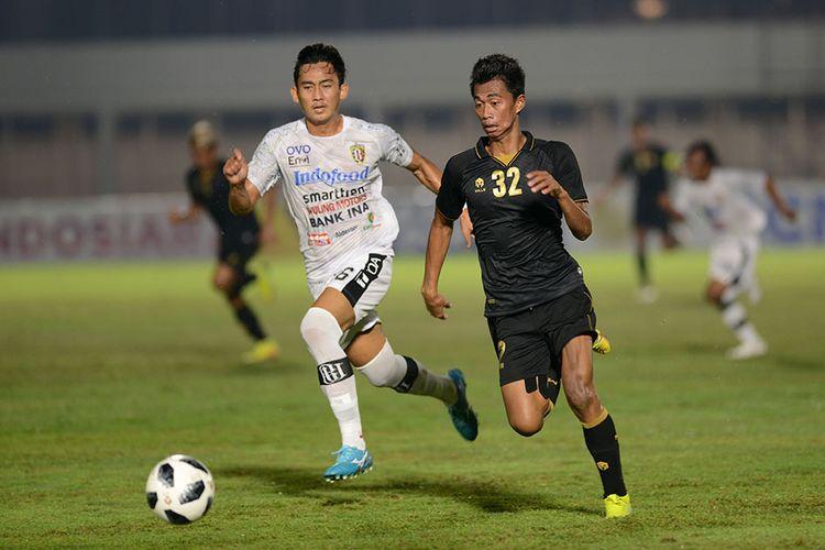 Pesepak bola Tim Nasional (Timnas) U-23 Kahar Kalu (kanan) berebut bola dengan pesepak bola klub Bali United Komang Tri dalam pertandingan uji coba di Stadion Madya, Gelora Bung Karno (GBK), Jakarta, Minggu (7/3/2021). Pertandingan dimenangkan Timnas U-23 dengan skor 3-1.
