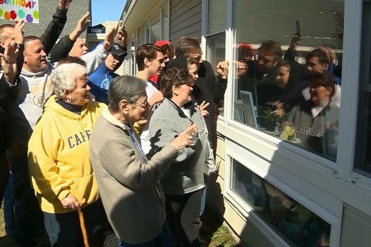 Perayaan ulang tahun ke 100 Millie Erickson, penghuni panti jompo Sterling Village di Sterling, Massachusetts, AS, dilakukan dari balik jendela.