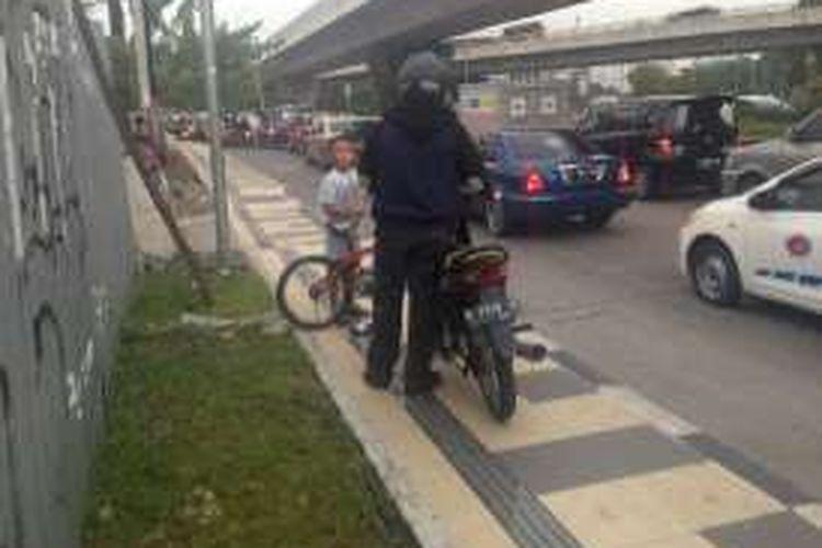 Benny, pengendara motor, diperingatkan oleh Daffa, bocah SD yang menghalangi trotoar dari pengendara motor di Jalan Sudirman, Kalibanteng, Semarang, Selasa (19/4/2016).