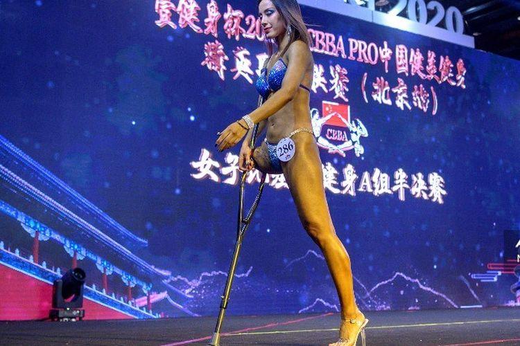 Foto tertanggal 11 Desember 2020 menampilkan Gui Yuna, wanita binaraga berkaki satu asal China, berjalan di atas arena kompetisi International Weightlifting Federation (IWF) Beijing 2020. Mantan atlet lompat jauh Paralimpiade Athena 2004 itu baru melakoni debut di kompetisi ini dan langsung juara.