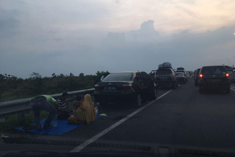 Sejumlah pemudik yang tak lagi bisa tertampung di tempat istirahat (rest area) Tol Cipali, Sabtu (1/7/2017) petang, memilih beristirahat di bahu jalan.