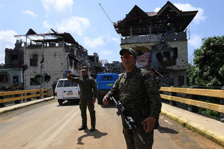 Prajurit Filipina berjaga di Jembatan Mapandi, Marawi di saat warga kota mulai berdatangan menengok rumah mereka di pusat pertempuran untuk mengambil barang-barang yang masih bisa diselamatkan.
