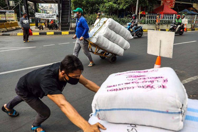 Pekerja menggunakan masker membawa karung berisi pakaian melintas di Tanah Abang di Jakarta Pusat, Senin (14/9/2020). PSBB kembali diterapkan tanggal 14 September 2020, berbagai aktivitas kembali dibatasi yakni aktivitas perkantoran, usaha, transportasi, hingga fasilitas umum.