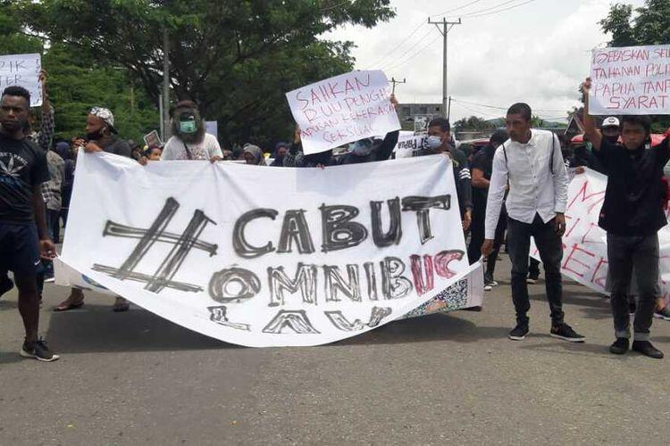 Ratusan mahasiswa Universitas Pattimura Ambon memblokade Jembatan Merah Putih saat berunjuk rasa menolak Undang-undang Omnibus Law Cipta Kerja di Ambon, Kamis (8/10/2020). Aksi unjuk rasa tersebut berakhir bentrok dengan aparat kepolisian