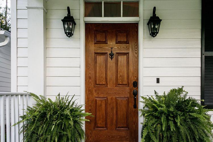 Ilustrasi tanaman di depan pintu masuk rumah.