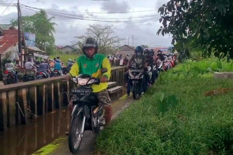 Sejumlah pesepeda motor menghindari penyekatan jalan dengan melewati jalan-jalan sempit dan bahkan melewati turap pari di Kota Pontianak, Kalimantan Barat, Senin (12/7/2021).