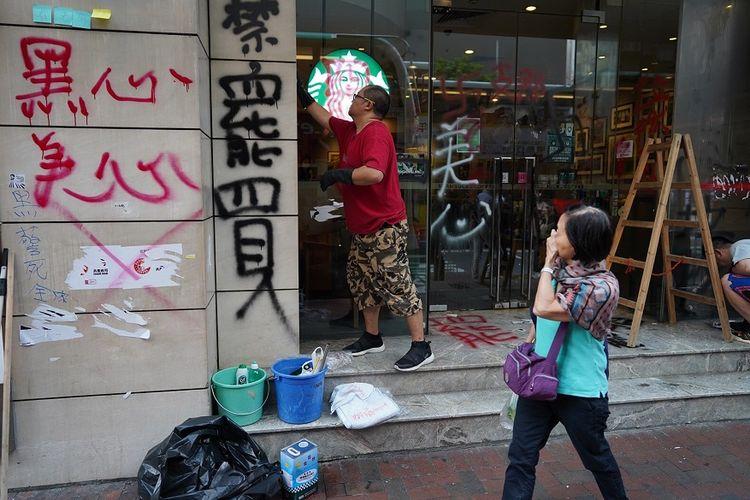Seorang pria membersihkan coretan yang dibuat oleh pengunjuk rasa di depan kedai kopi Starbucks di Hong Kong, Senin (30/9/2019).