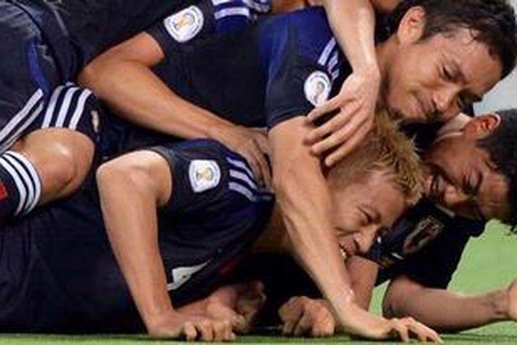 Gelandang Jepang, Keisuke Honda (bawah) dikerubuti rekan-rekannya,a termasuk Shinji Kagawa (kanan), usai dia mencetak gol penalti ke gawang Australia, Selasa (4/6/2013), pada kualifikasi Piala Dunia zona Asia. Hasil imbang ini pastikan Jepang raih tiket putaran final Piala Dunia 2014.