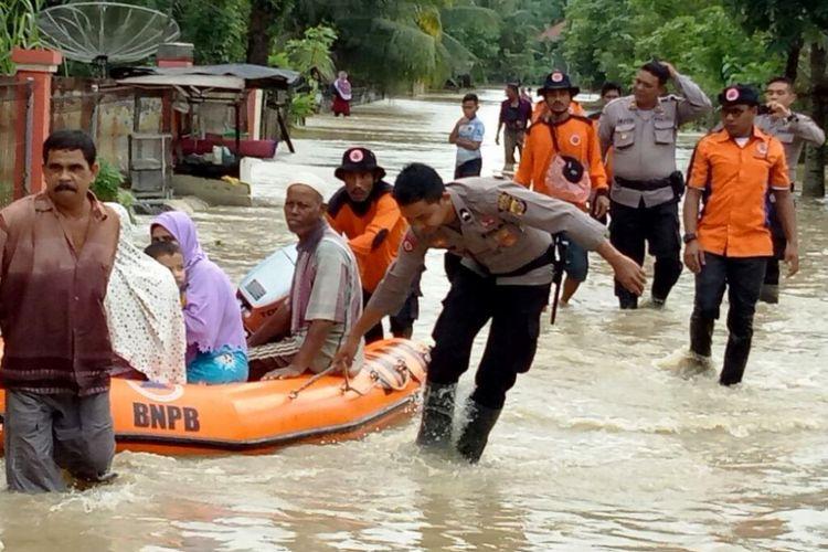 Polisi dan Tim BPBD Aceh Utara mengevakuasi korban banjir di Desa Hagu, Kecamatan Matangkuli, Aceh Utara, Sabtu (2/12/207).