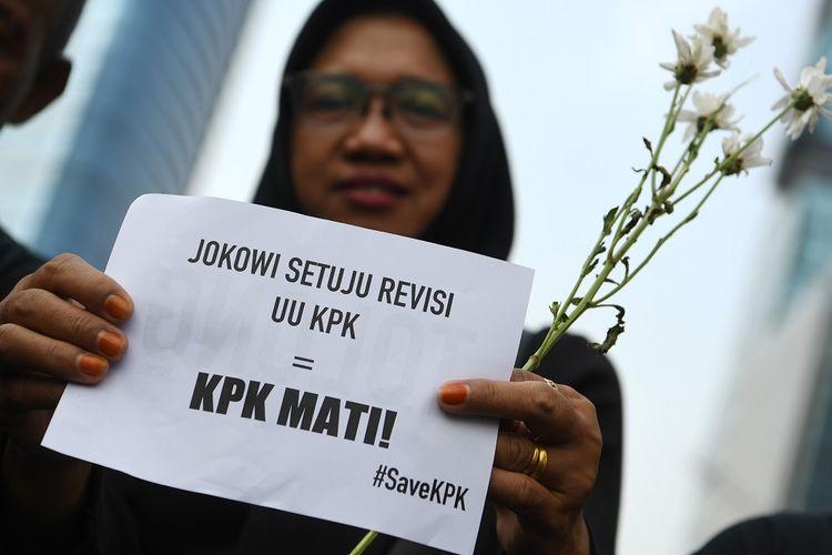 Pegawai KPK membawa bunga dan poster untuk dibagikan kepada warga pada melakukan aksi saat Hari Bebas Kendaraan Bermotor  di kawasan Bundaran HI Jakarta, Minggu (8/9/2019). Aksi tersebut untuk menolak revisi UU KPK yang dianggap melemahkan kewenangan lembaga anti rasuah itu. ANTARA FOTO/Wahyu Putro A/hp.