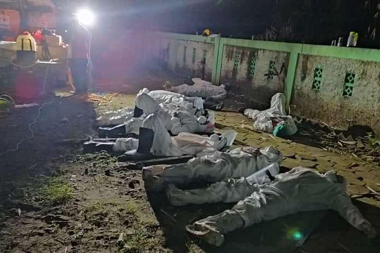 KELELAHAN—Banyaknya jenazah yang harus dimakamkan secara prokes covid-19 membuat relawan di Kota Madiun kelelahan. Nampak tim tidur di area pemakaman untuk menghilangkan lelah setelah seharian berjibaku menguburkan belasan jenazah secara prokes covid-19.