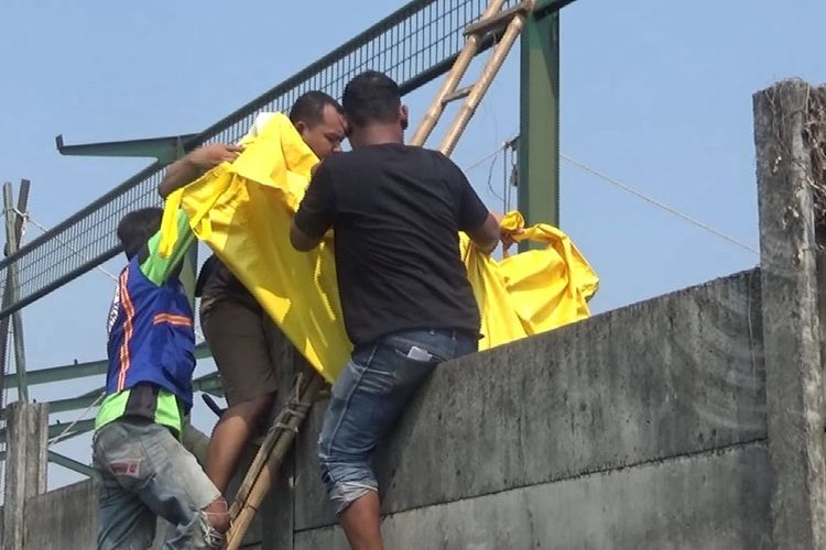Proses evakuasi sosok jenazah perempuan tanpa identitas dari belakang bangunan pabrik ke dalam area pabrik PT Clasik Prima Carpet Industries (CPCI) di Mojoagung, Jombang, Jawa Timur, Rabu (27/11/2019) pagi.