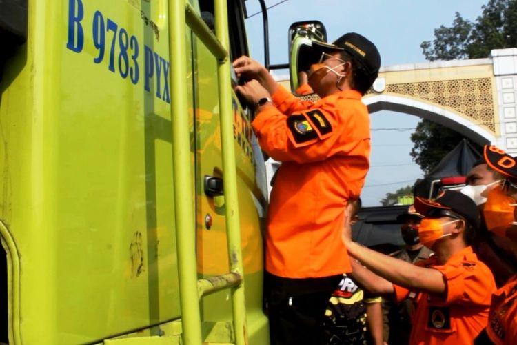 Bupati Cianjur Herman Suherman menaiki bodi kendaraan untuk memeriksa pengendara truk tronton di perbatasan Cianjur-Bandung Barat, dalam gat penyekatan larangan mudik lebaran, Kamis (6/5/2021).
