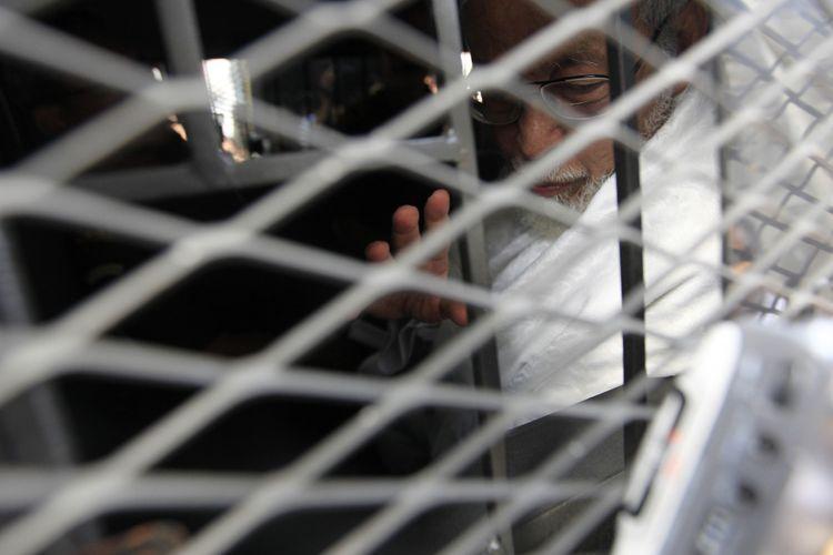 Ustad Abu Bakar Baasyir dibawa ke dalam mobil tahanan usai menjalani sidang kasus terorisme di Pengadilan Negeri Jakarta Selatan, Kamis (16/6/2011).Baasyir dijatuhi vonis 15 tahun penjara oleh Majelis Hakim, karena dinyatakan terbukti terlibat dalam perencanaan pelatihan bersenjata api di Pegunungan Jalin Jantho di Aceh Besar, hingga mengumpulkan pendanaan sebesar Rp 1 miliar untuk pelatihan tersebut.