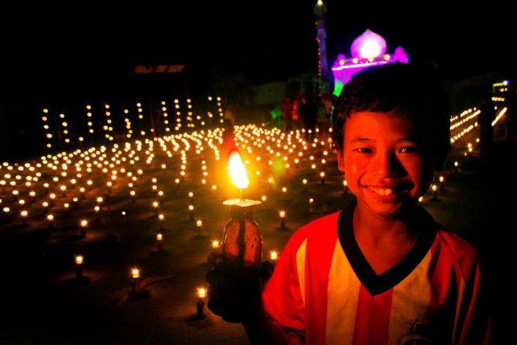 Seorang anak bergembira turut meikmati malam pasang lampu di Gorontalo. Tradisi ini diturunkan dari generasi ke generasi