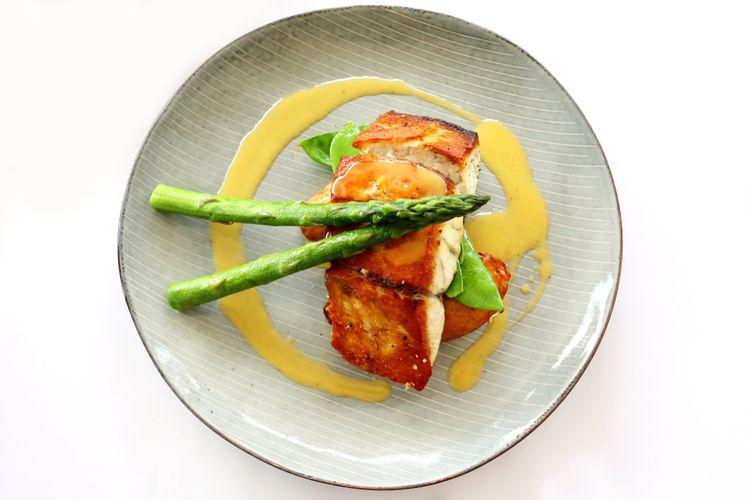 Ilustrasi ikan barramundi filet panggang, lengkap dengan asparagus.