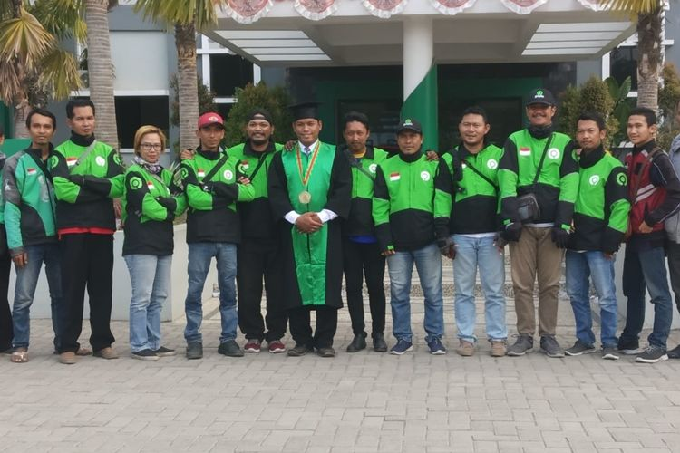 Driver Ojek Online, Badrut Tamam, Usai Wisuda Program Pasca Sarjana di Kampus IAIN Jember, Jawa Timur, Disambut Rekan- Rekannya.