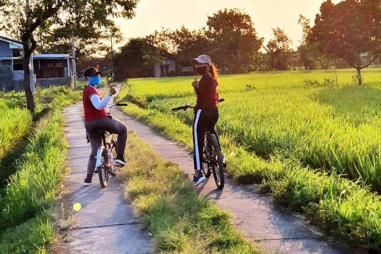 Ibu-ibu bersepeda saat sore hari dengan mengenakan masker.