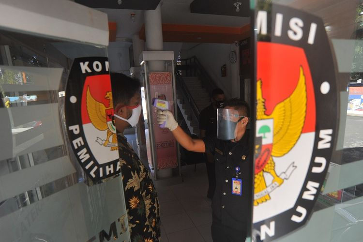 Petugas menggunakan pelindung wajah mengecek suhu tubuh staf yang datang di Kantor Komisi Pemilihan Umum (KPU) Sumatera Barat, di Padang, Jumat (10/7/2020). KPU pusat menyiapkan perlengkapan APD dan fasilitas kesehatan untuk panitia dan peserta pemilu di daerah sebagai upaya penerapan protokol kesehatan COVID-19 selama Pilkada serentak 2020. ANTARA FOTO/Iggoy el Fitra/pras.