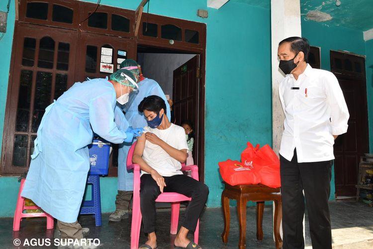 Foto dokumentasi fotografer Presiden, Agus Suparto, memperlihatkan Presiden Joko Widodo meninjau vaksinasi door to door di Madiun, Jawa Timur, Kamis (19/8/2021).