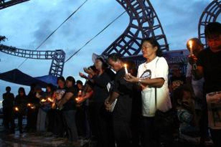Sambil memegang lilin dan berdoa serta menangis, warga pulau Bangka, Minahasa Utara melakukan aksi damai di Tugu Boboca Manado, menolak rencana eksplorasi tambang di pulau mereka.