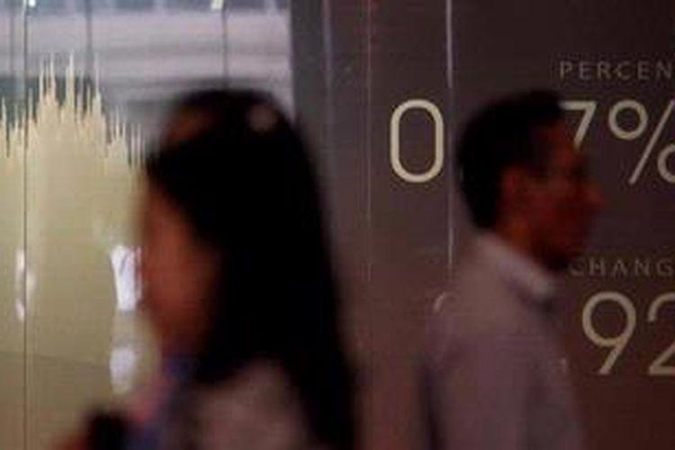 Karyawan melintas di dekat monitor yang menunjukkan pergerakan indeks di Bursa Efek Indonesia, beberapa waktu lalu