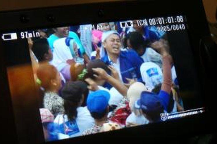 Rekaman video wartawan memperlihatkan seorang pria berjaket Partai Demokrat dikerumuni massa saat ia membagikan uang dari dalam saku celananya pada saat kampanye Partai Demokrat di Kota Palembang, Selasa (1/4/2014).