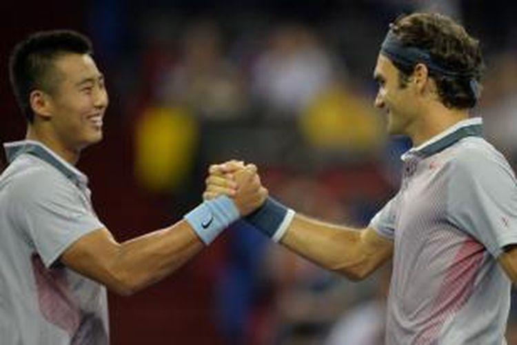 Petenis Swiss, Roger Federer (kanan), bersalaman dengan petenis China, Zhang Ze, setelah berhasil meraih kemenangan di babak pertama Shanghai Masters di nomor ganda. Mereka mengalahkan Kevin Anderson/Dmitry Tursunov, 6-2, 6-1, Senin (7/10/2013).