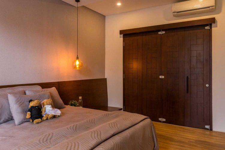 Kamar tidur Dast Residence tampak sangat hangat dengan earthy tone