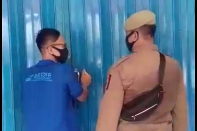 Petugas Satpol PP Makassar saat memerintahkan penjaga toko peralatan sekolah untuk membuka pintu karena beroperasi secara diam-diam di hari pertama PSBB, Jumat (24/4/2020).