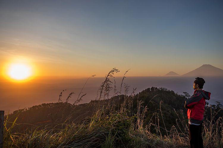 Seorang pengunjung menikmati momen sunset yang tersaji di Puncak Gunung Kunir Purworejo.