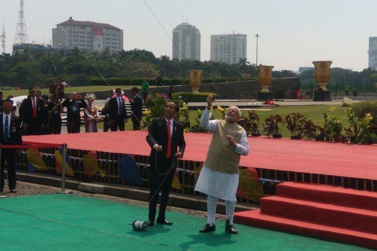 Joko Widodo dan Sri Narendra Modi tampak gembira ketika diminta memainkan layang-layang yang bergambar lambang 70 tahun persahabatan antara Indonesia dan India.
