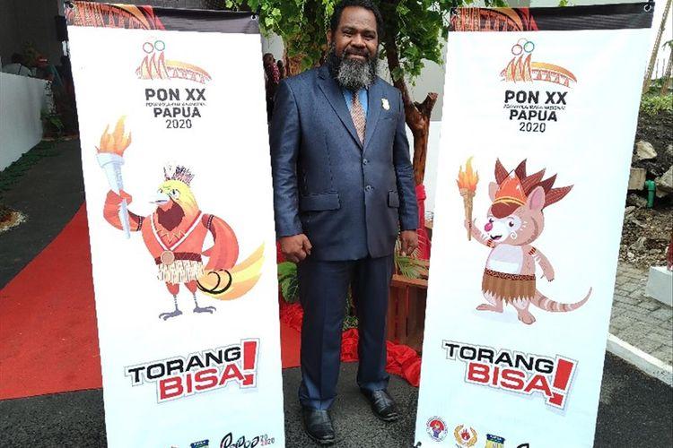 Anggota DPR Papua Ireneus Liku Bolly berfoto di antara banner logo dan maskot PON XX 2020 yang baru diluncurkan Gubernur Papua Lukas Enembe, di Kantor DPR Papua, Kamis (1/08/2019)