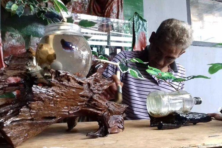 Riaman (49) saat membersihkan kayu hiasa untuk aquarium ikan cupang buatannya, Selasa (24/11/2020).