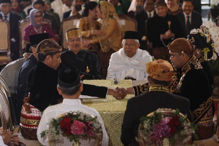 Presiden Joko Widodo (ketiga kiri) menikahkan putrinya, Kahiyang Ayu (kanan) dengan Bobby Nasution (kedua kanan) disaksikan Wakil Presiden Jusuf Kalla (keempat kiri) dan Ketua MUI KH Maruf Amin (keempat kanan) saat ijab kabul di Gedung Graha Saba, Sumber, Solo, Jawa Tengah, Rabu (8/11/2017).