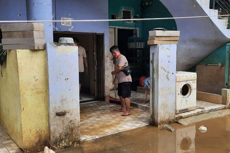 Warga Cipinang Melayu, Jakarta Timur, mulai membersihkan sisa-sisa banjir, Minggu (21/2/2021).
