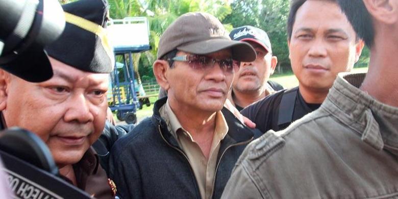Terpidana korupsi Bupati Kepulauan Aru Theddy Tengko (memakai topi dan kacamata hitam) saat tiba di Ambon, Maluku dan hendak dibawa ke Lembaga Pemasyarakatan Ambon, Rabu (29/5/2013). Tengko yang telah divonis bersalah mengkorupsi uang rakyat oleh Mahkamah Agung sejak 10 April 2012, akhirnya berhasil dieksekusi  kemarin oleh tim yang terdiri dari kejaksaan, kepolisian, dan TNI AD.