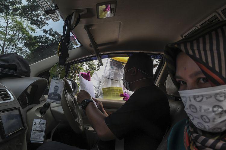 Petugas Dinas Kesehatan Kota Depok melakukan pengecekan saat tes cepat (rapid test) COVID-19 dengan sistem drive thru kepada pengguna kendaraan di Cimanggis, Depok, Jawa Barat, Minggu (29/3/2020). Tes dengan sistem tersebut dilakukan guna mempercepat proses pemeriksaan dan mempersempit penyebaran penularan COVID-19 di wilayah Depok dan sekitarnya.