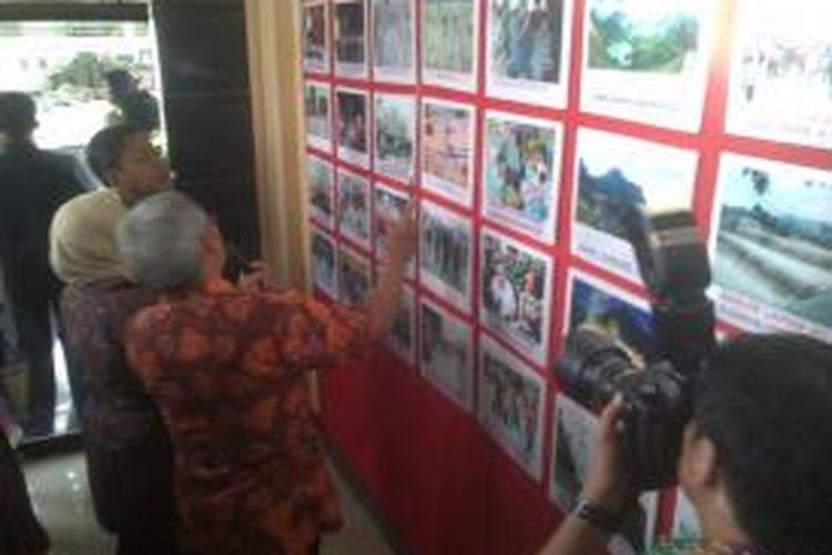 Wakil Presiden Boediono (ujung) saat mendengarkan paparan foto kronologi erupsi Gunung Kelud oleh Wakil Bupati Kediri Masykuri Iksan di gedung teater Kelud Desa Sugihwaras Kecamatan Ngancar, Minggu (27/4/2014).