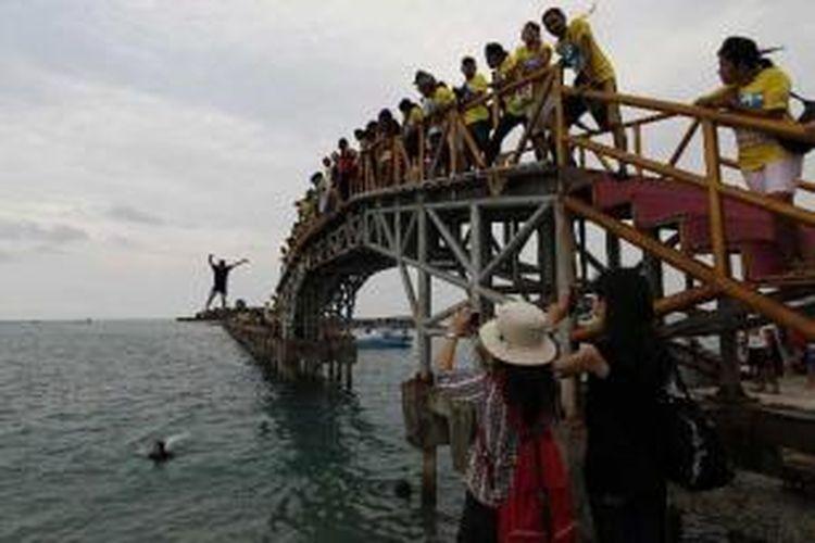 Wisatawan mandi dan bermain di jembatan yang menghubungkan Pulau Tidung Besar dan Pulau Tidung Kecil, di Kepulauan Seribu, Sabtu (14/5/2011). Pulau ini kian dikenal sebagai salah satu destinasi wisata bahari. Pada hari libur, pulau yang memiliki lebar sekitar 200 meter dan panjang hanya 5 kilometer, ini ramai dikunjungi wisatawan.