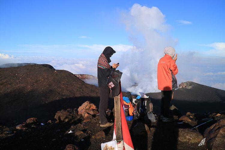Pendaki di puncak Gunung Slamet, Jawa Tengah dengan latar belakang kawah gunung api. Gunung Slamet merupakan salah satu gunung api aktif di Indonesia.