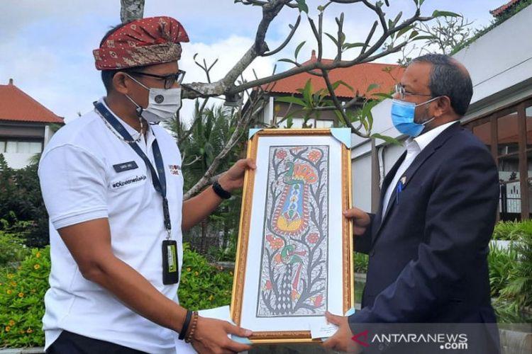 Minister of Tourism and Creative Economy, Sandiaga Salahuddin Uno, hands a souvenir to Indian Ambassador to Indonesia, Shri Manoj Kumar Bharti, in Badun on Wednesday, March 17.