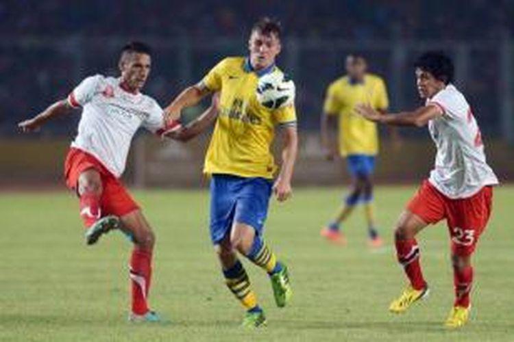 Pemain Arsenal Aaron Ramsey (tengah) dikepung dua pemain Indonesia, Raphael Maitimo (kiri) dan Rizky Pellu, dalam laga persahabatan di Stadion Utama Gelora Bung Karno, Jakarta, Minggu (14/7/2013. Indonesia dicukur habis oleh Arsenal 0-7.