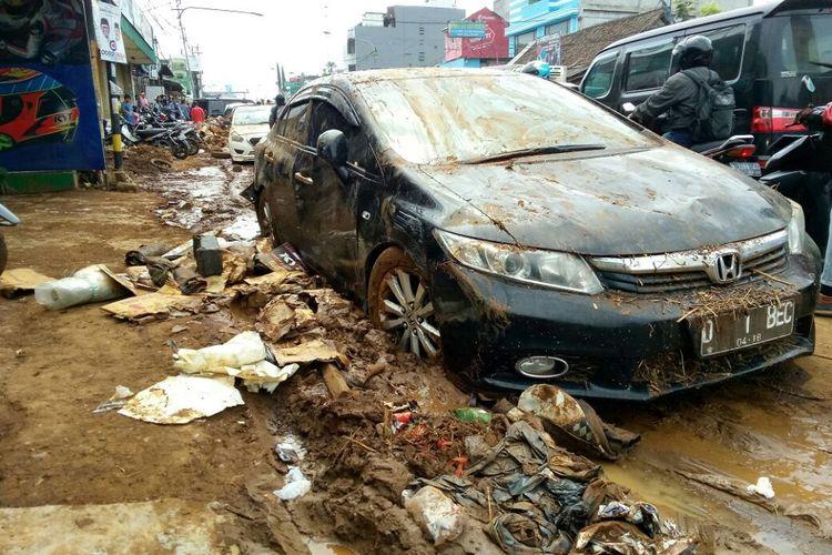 Sebuah kendaraan roda empat terlihat kotor dengan lumpur dan sampah di pinggirannya. Itu merupakan salah satu kendaraan yang sudah dievakuasi setelah sebelumnya bertumpuk terbawa arus banjir yang masuk ke gudang furnitur di Jalan AH Nasution, Kelurahan Cicaheum, Kecamatan Kiaracondong.