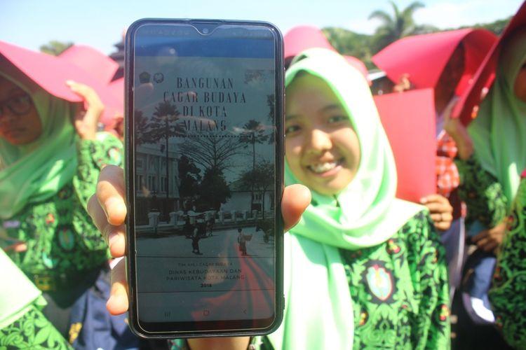 Andini Aviolla Belindawati (13) salah satu siswa saat menunjukkan sebuah judul buku dalam peluncuran perpustakaan digital dan pemecahan rekor MURI di Balai Kota Malang, Kamis (12/12/2019).
