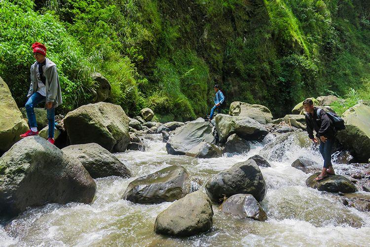 Menyeberangi sungai menuju Air Terjun Kedung Kayang salah satunya bisa dilakukan dengan melompat di antara bebatuan. Berani?