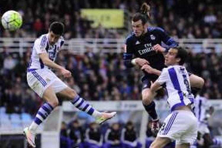 Pemain Real Madrid, Gareth Bale (tengah), berduel dengan pemain Real Sociedad dalam lanjutan La Liga di Estadio Municipal de Anoeta, Sabtu (30/4/2016).